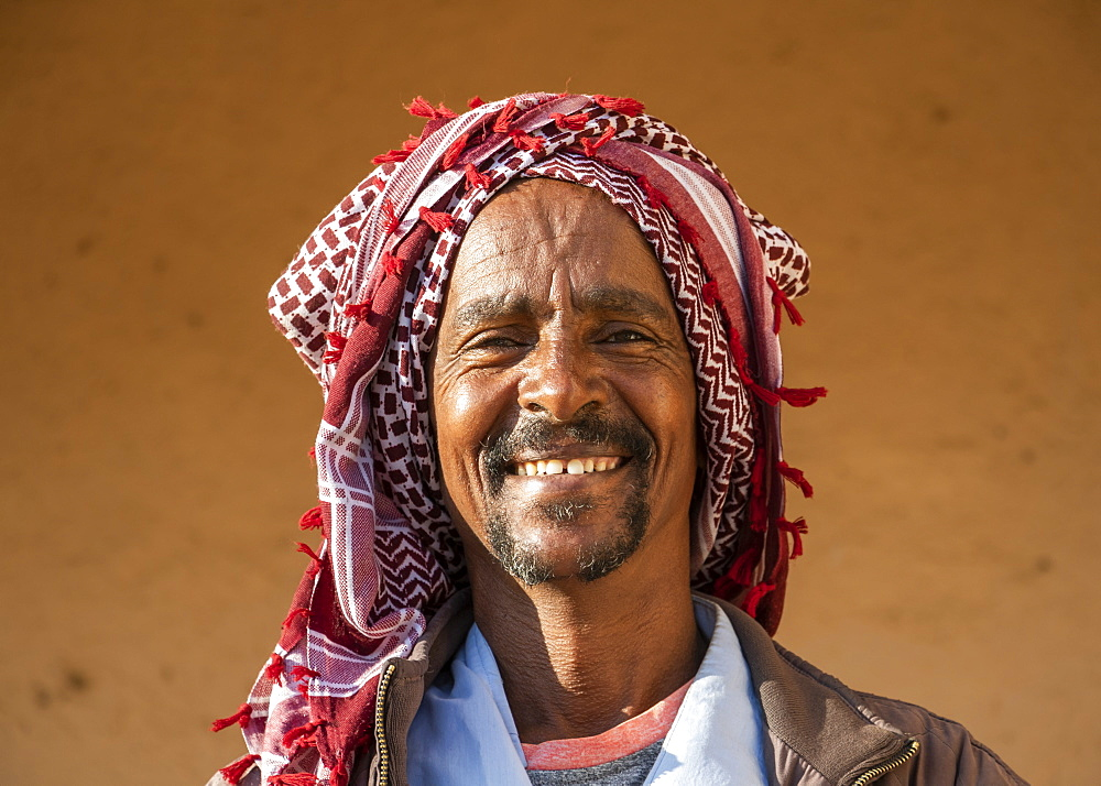 Portrait of an Eritrean man smiling with a headscarf on his head, Monday livestock market, Keren, Anseba Region, Eritrea