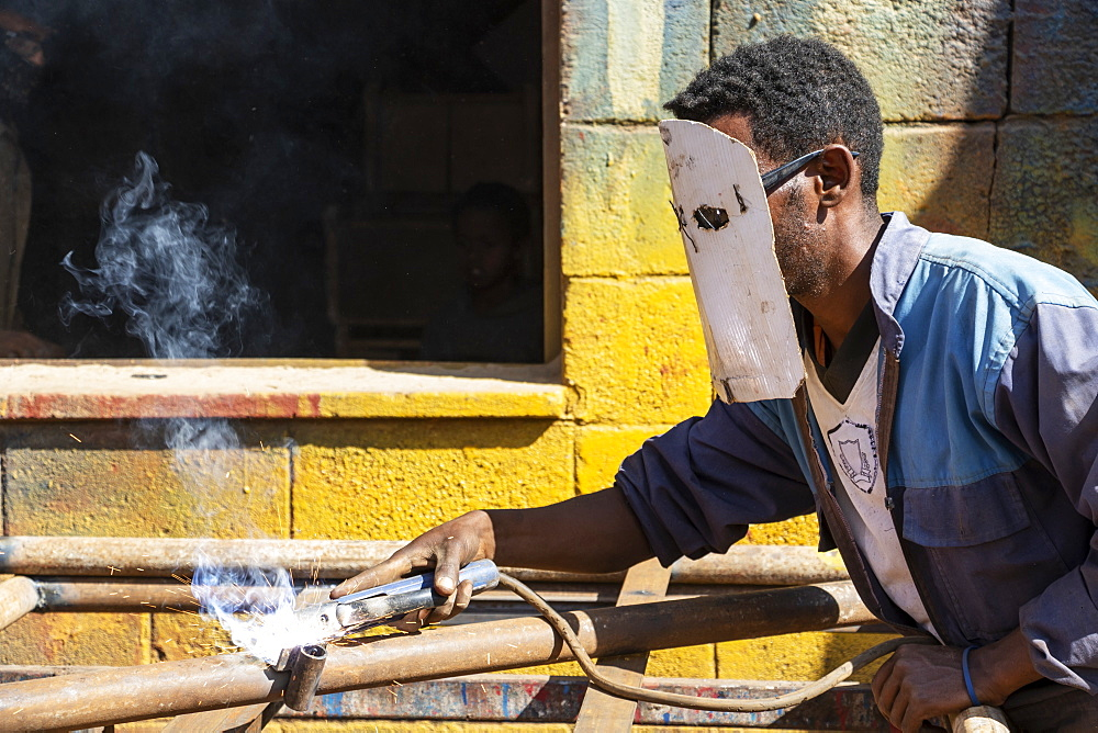 Welder at the Medeber Market, where artisans recycle old tyres and tins to make new artifacts, Asmara, Central Region, Eritrea