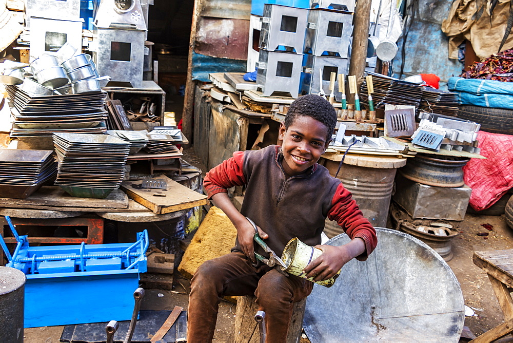 Eritrean boy cutting a can at the Medeber Market, where artisans recycle old tyres and tins to make new artifacts, Asmara, Central Region, Eritrea - 1116-43361