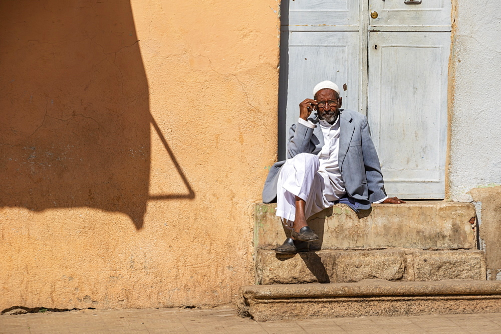 Eritrean man sitting on steps outside a door, Asmara, Central Region, Eritrea