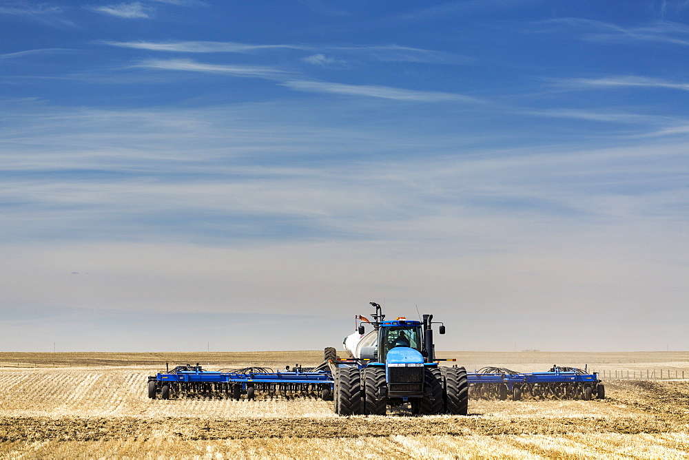 Tractor with air seeder, seeding a stubble field with blue sky and hazy clouds, near Beiseker, Alberta, Canada