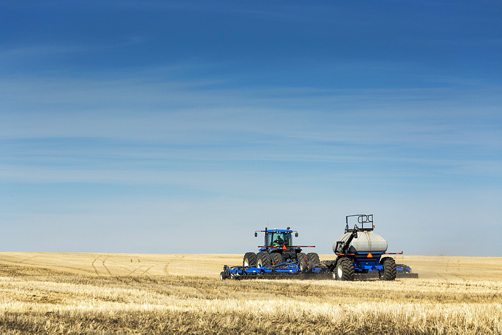 Tractor with air seeder in field with blue sky and hazy clouds, near Beiseker, Alberta, Canada