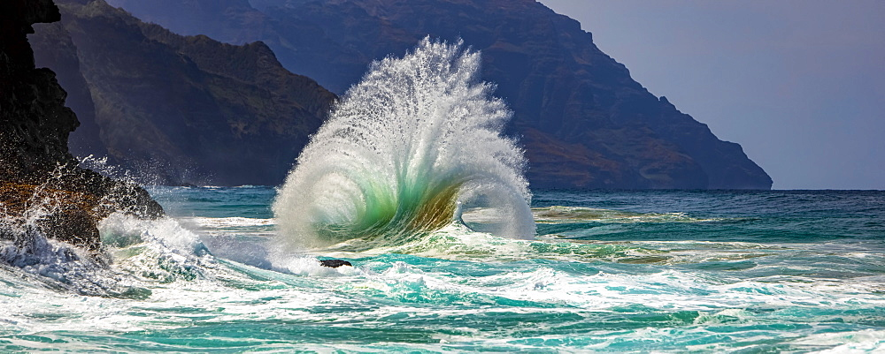 Large ocean wave crashes into rock along the Na Pali Coast, Kauai, Hawaii, United States of America