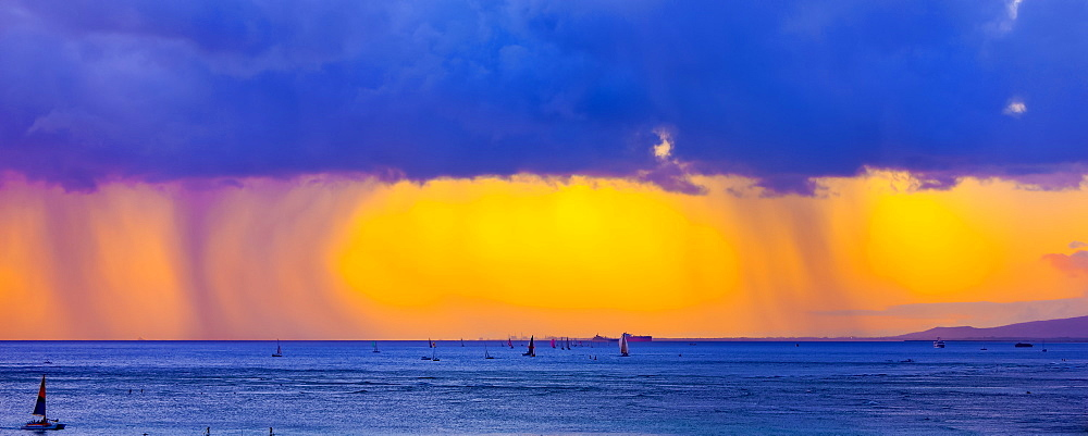 Storm clouds with rain and clouds glowing a bright yellow at sunset off Waikiki Beach with a silhouetted sailboats in the water, Honolulu, Oahu, Hawaii, United States of America