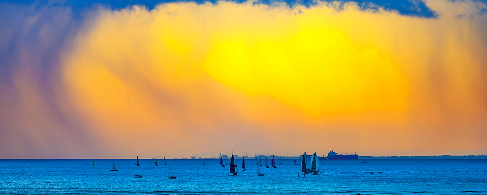 Clouds glowing a bright yellow at sunset off Waikiki Beach with a silhouetted sailboats in the water, Honolulu, Oahu, Hawaii, United States of America