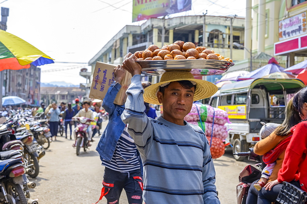 Young man carrying food on his head in the busy street, Lashio, Shan State, Myanmar