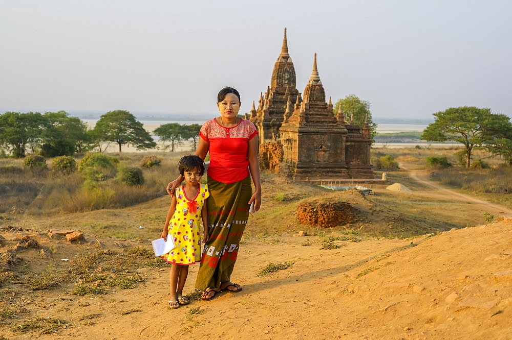 Portrait of a mother and daughter while selling drawings, a Buddhist temple the background, Bagan, Mandalay Region, Myanmar