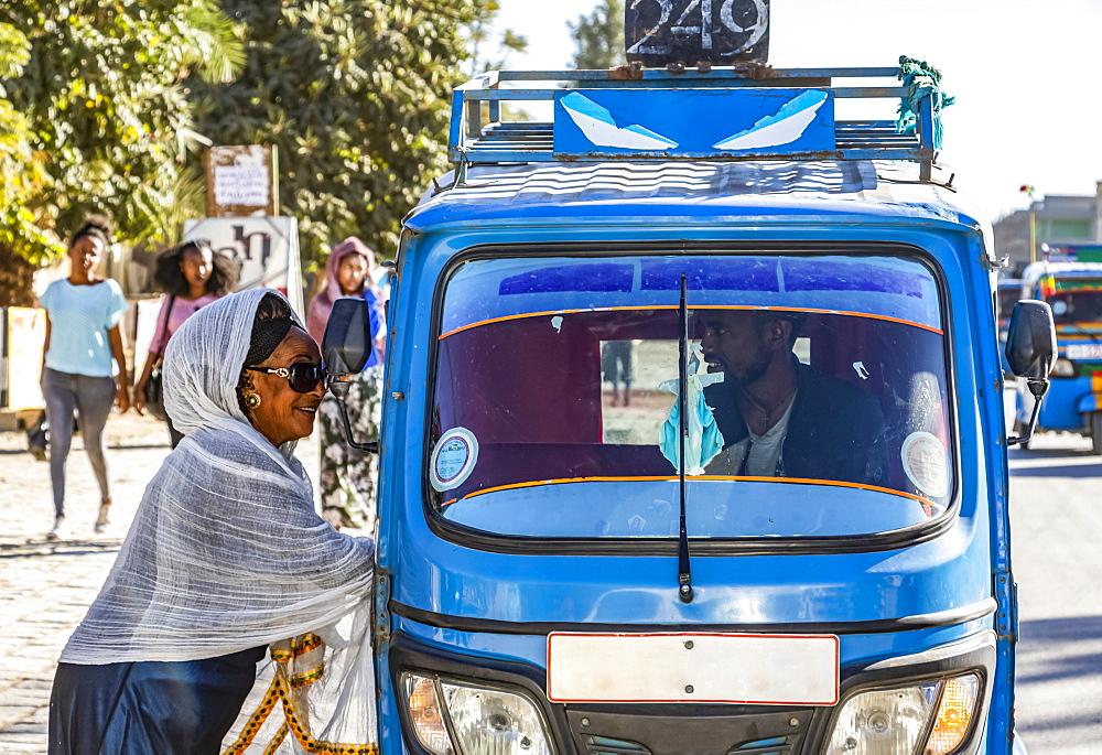 Woman by an auto rickshaw talking to the driver through the window, Wukro, Tigray Region, Ethiopia
