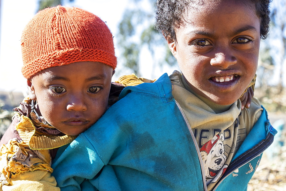 Ethiopian girl carrying a little boy, Simien Mountains, Amhara Region, Ethiopia