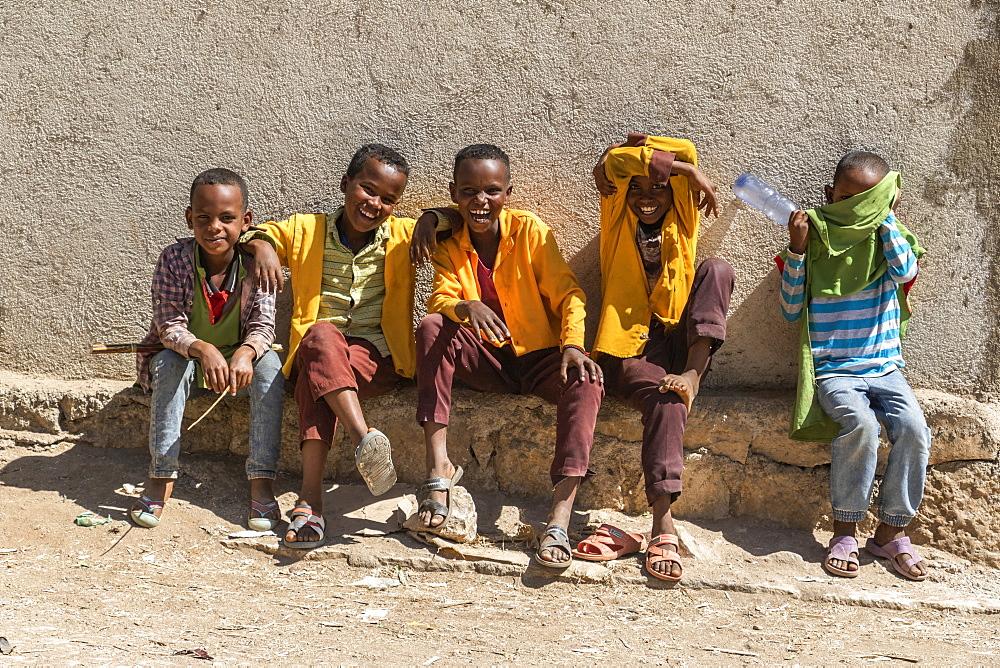 Ethiopian boys sitting and laughing, Harar Jugol, the Fortified Historic Town, Harar, Harari Region, Ethiopia