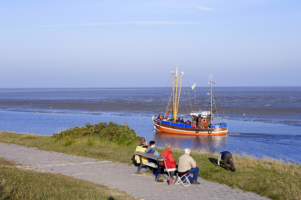 Tourists on bench and shrimp cutter, Neuharlingersiel, Lower Saxony, Germany