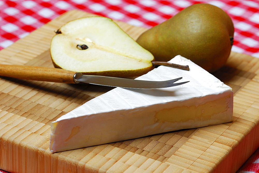 Brie cheese, pear in halves, knife