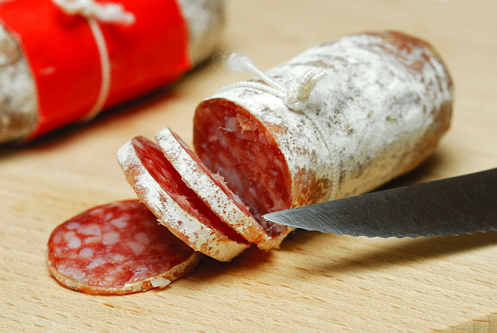 Salametti and knife, wooden plate / salami