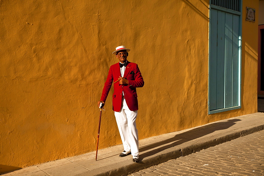 the actor Pedro Pablo Perez with red suit, hat and cigar in Havana, Cuba, Caribbean / Havanna