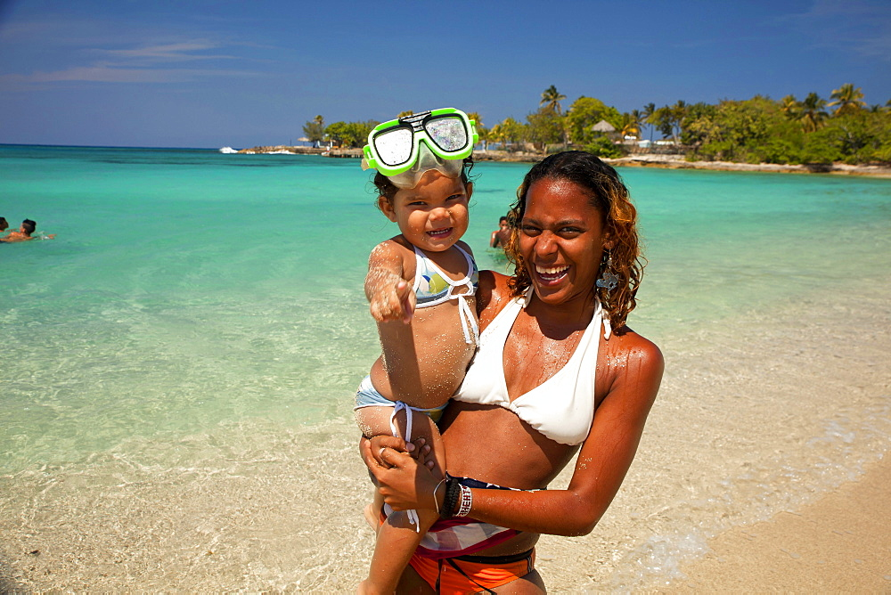 smiling young cuban woman with small child at Bacuranao Beach, Playas del este, Havana, Cuba, Carribean