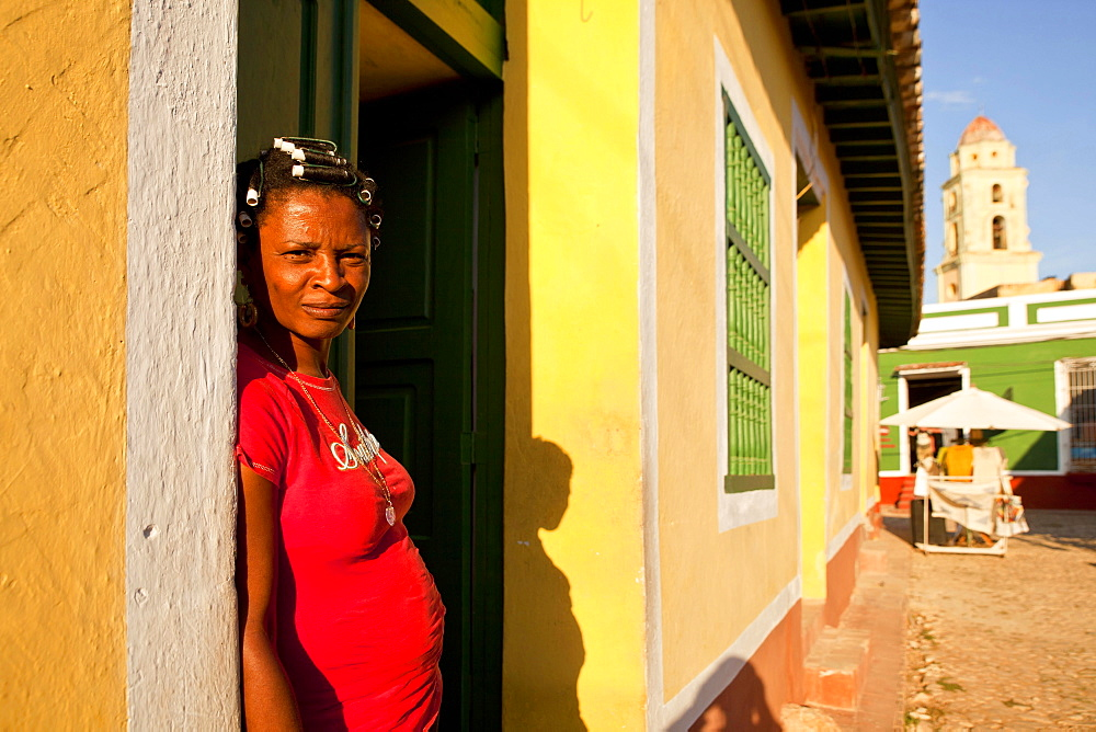 woman in her home entrance and the bell tower of the Convento de San Francisco in Trinidad, Cuba, Caribbean