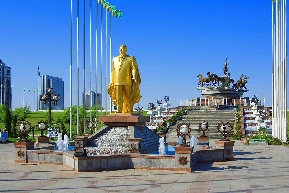 Gold covered statue of president Turkmenbasy, in front of monument of the 10th anniversary of Independence, Ashgabat, Turkmenistan / Asgabat