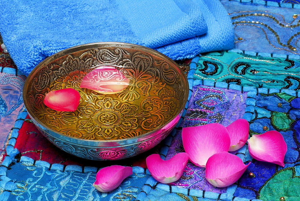 Massage oil in bowl with Rose petals
