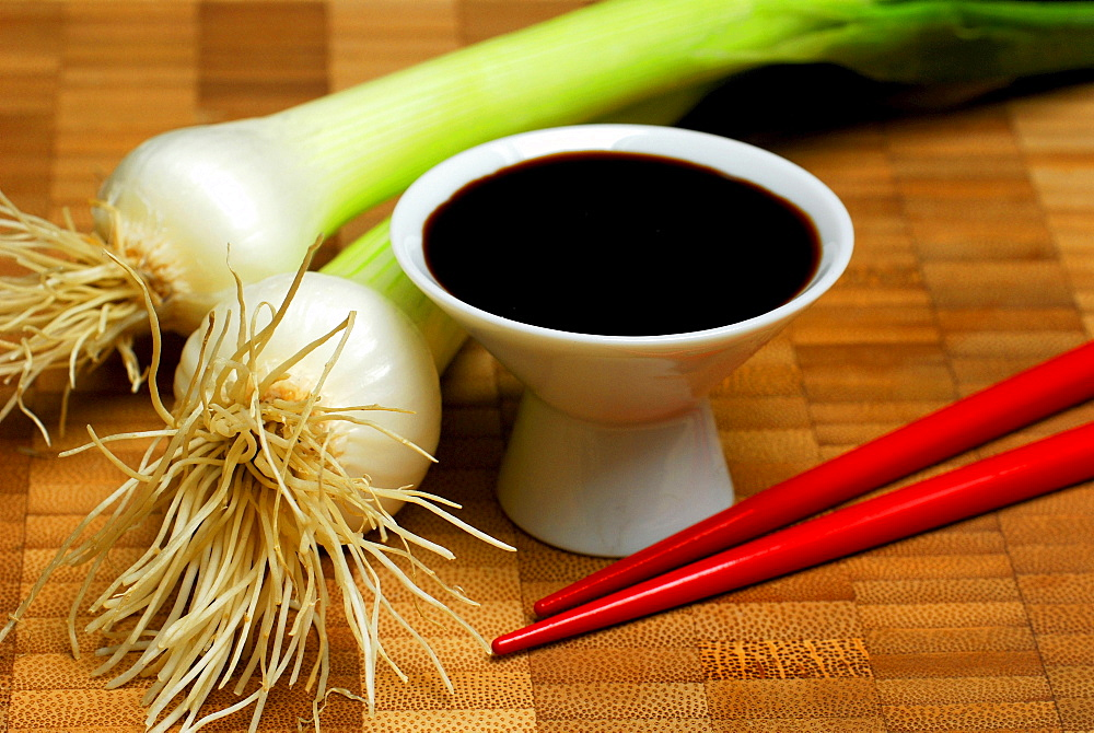 Soy sauce in bowl, chopsticks and spring onions
