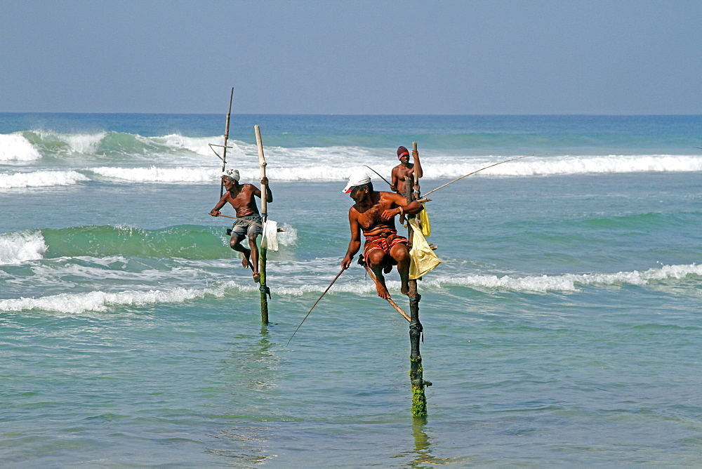 Stilt fishermen and Indian Ocean, Weligama, Sri Lanka, Asia
