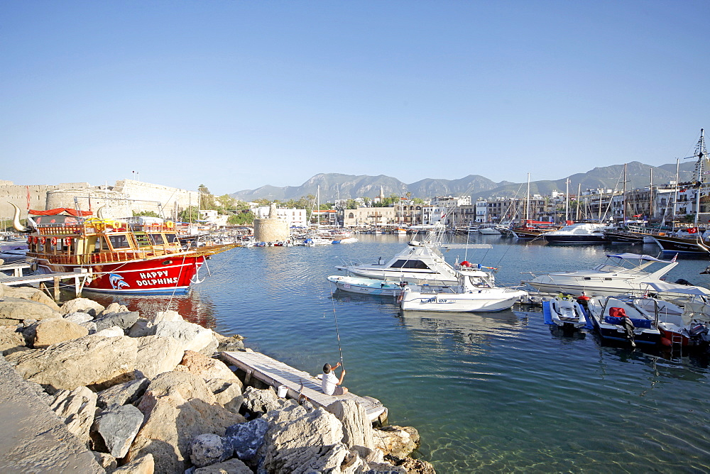 Boy fishing and boats in harbour, Kyrenia, Northern Cyprus, Mediterranean, Europe