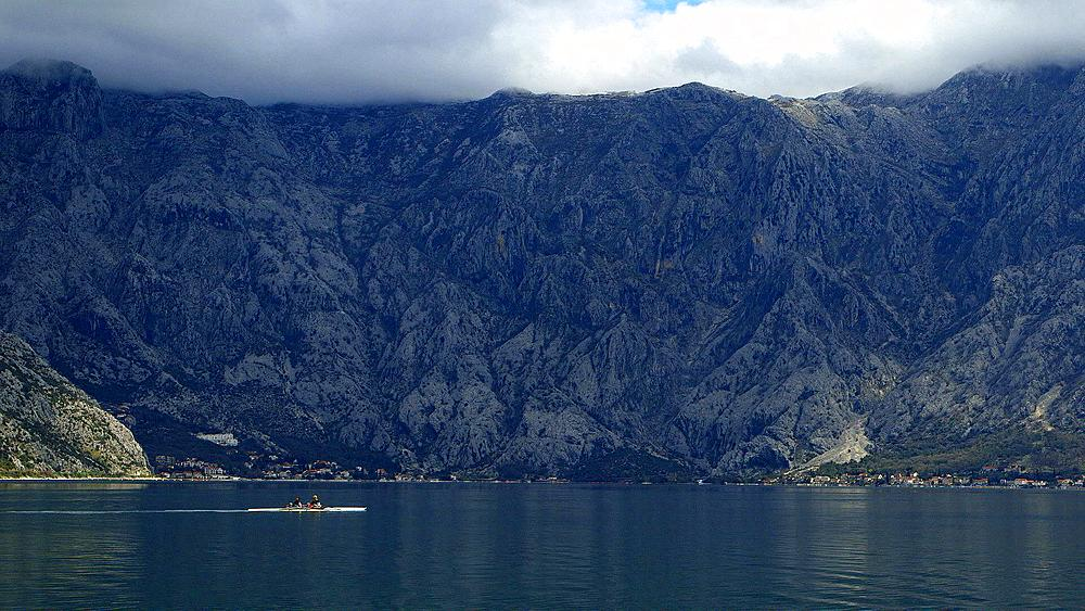 Rowing boat on kotor bay & mountain range, kotor bay, Montenegro