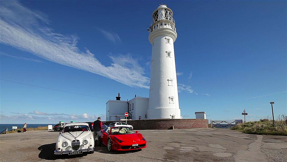 White mk ii jaguar, red ferrari 458 spider cars & lighthouse, Flamborough Head, North Yorkshire, England