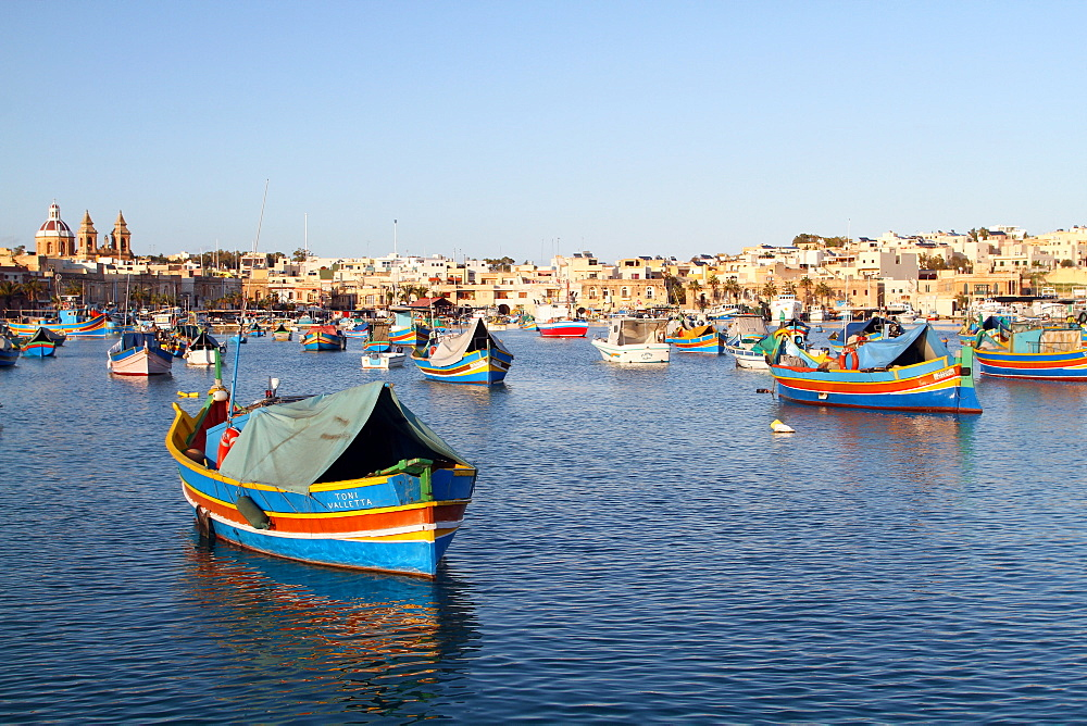 Multi-coloured fishing boats and town, St. Julians, Malta, Mediterranean, Europe