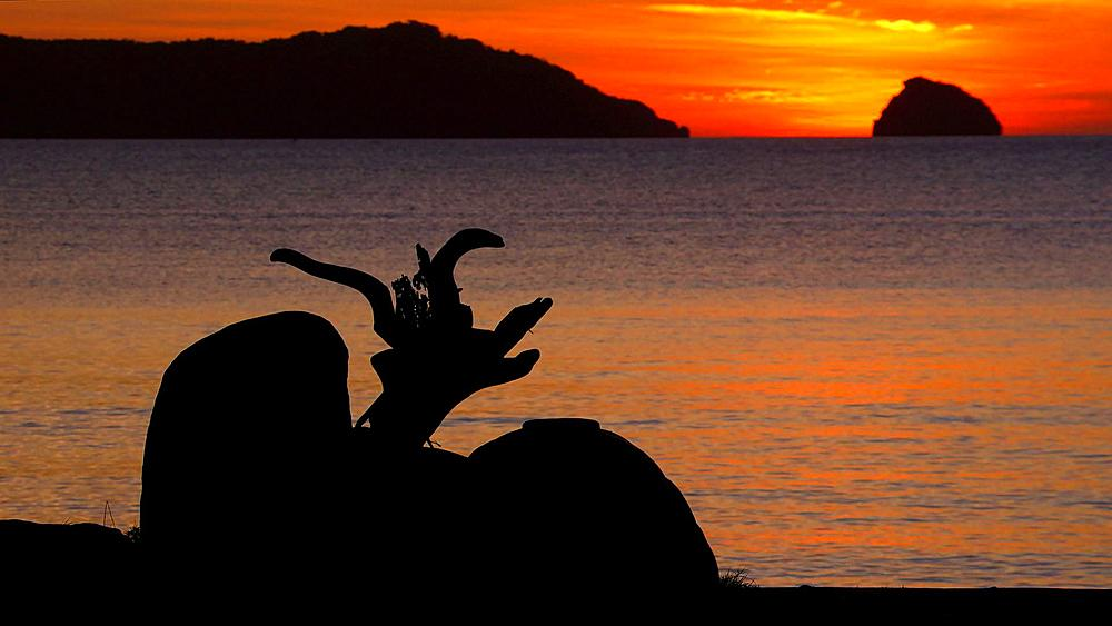 Silhouetted woman & red sunset over islands, El Nido, Palawan, Philippines