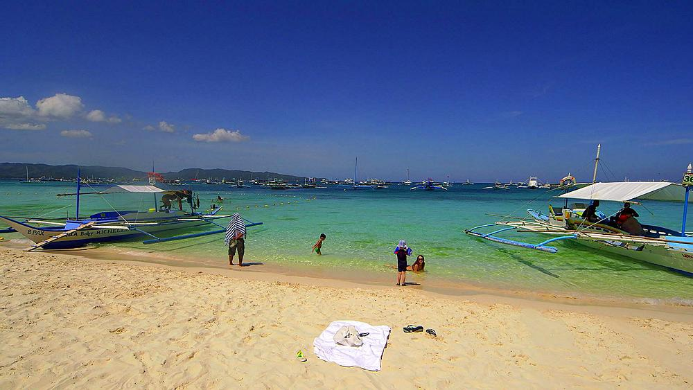Boy photographs mother with tourists jukung boats at shore, white beach, Boracay Island, Philippines