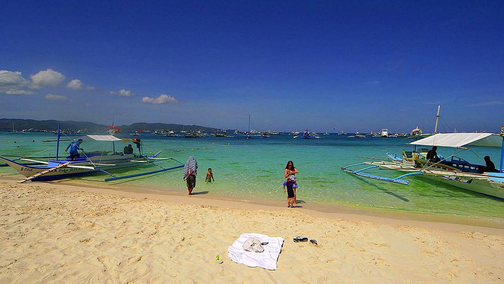Tourists jukung boats at shore, white beach, Boracay Island, Philippines