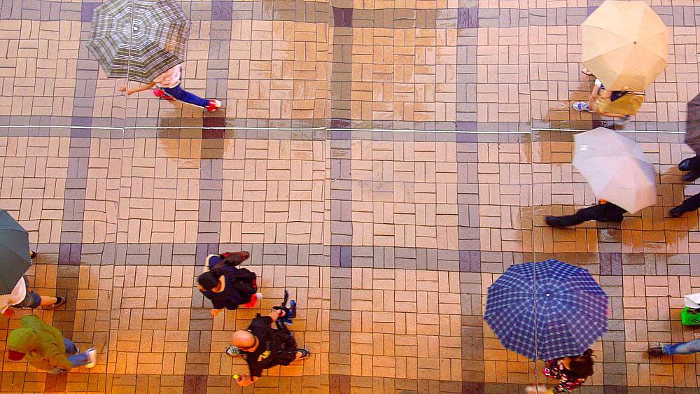 Mirrored Reflection Looking Down On Pedestrians With Umbrellas, Tsim Sha Tsui, Kowloon, Hong Kong, China