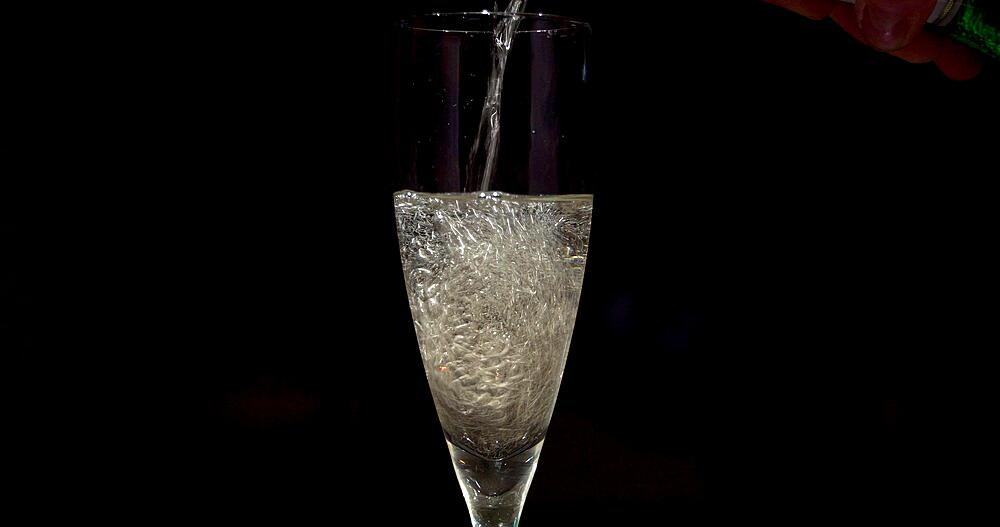 Pouring sparkling wine into glass, kitchen activities