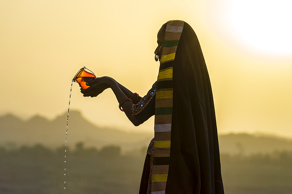 Ahir Woman in traditional colorful cloth pouring water at sunset, Great Rann of Kutch Desert, Gujarat, India, Asia - 1131-1251