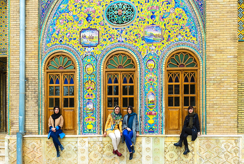 Group of young Iranian women seated in front of ceramic tiles, Golestan Palace, UNESCO World Heritage Site, Tehran, Islamic Republic of Iran, Middle East