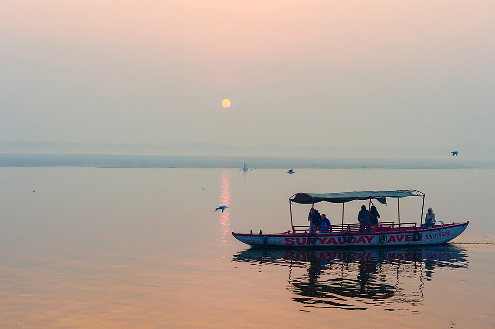 Small boats on Ganges River at sunset, Varanasi, Uttar Pradesh, India