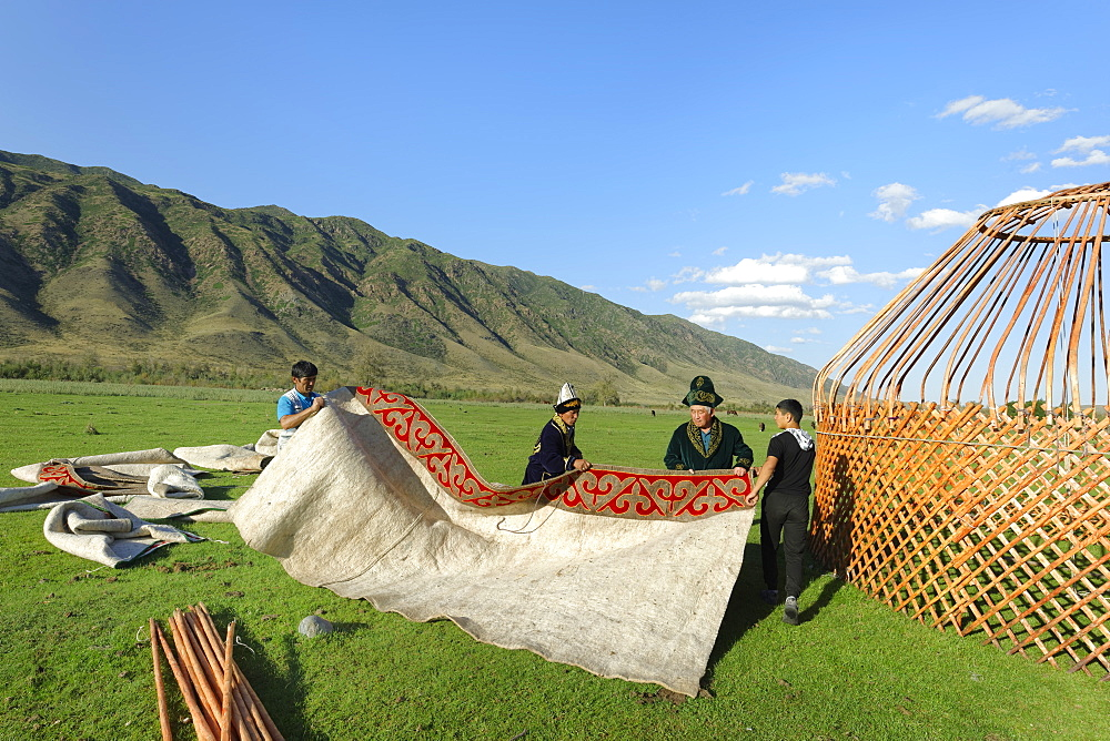 Kazakh men putting up a yurt, Sati village, Tien Shan Mountains, Kazakhstan