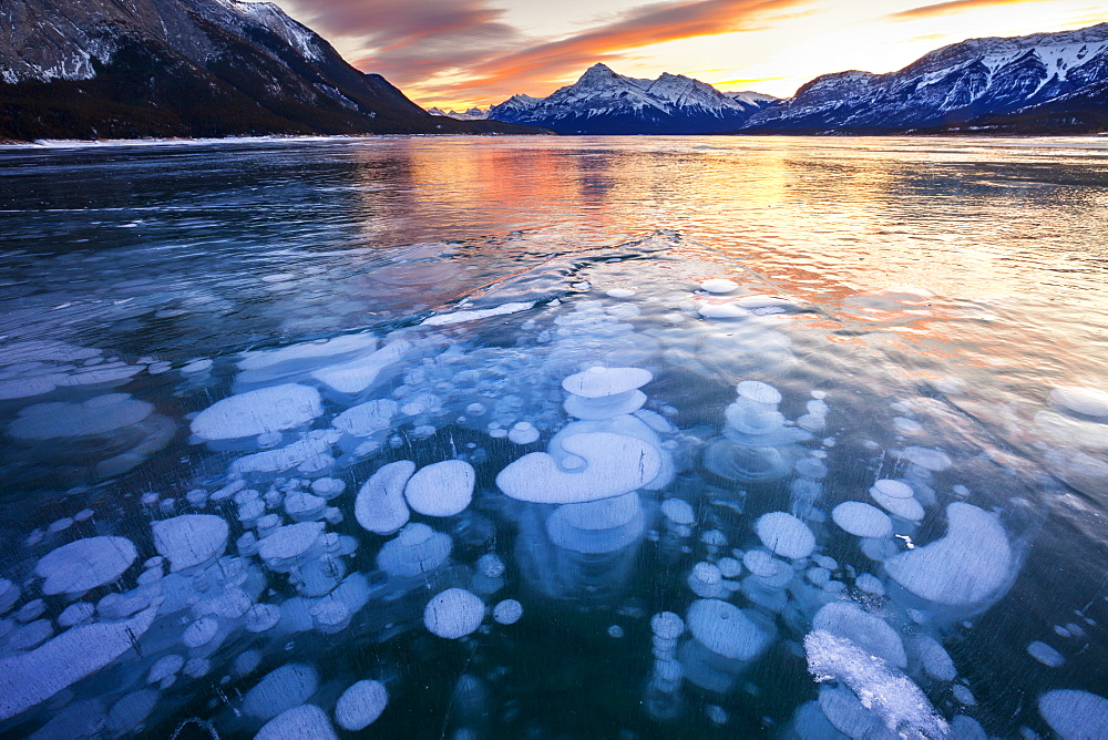 Bubbles and Cracks in the Ice with Elliot Peak in the Background at Sunset, Abraham Lake, Alberta, Canada, North America