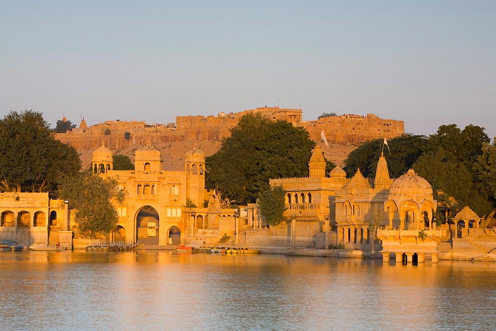 Jaisalmer Fortress and Gadsisar Lake illuminated at sunrise, Jaisalmer, Rajasthan, India, Asia