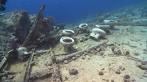 Toilet bowls on sea floor by wreck of Thistlegorm; diver sits on them