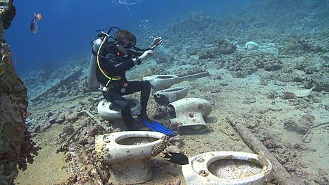 Toilet bowls on sea floor by wreck of Thistlegorm; diver leaves them