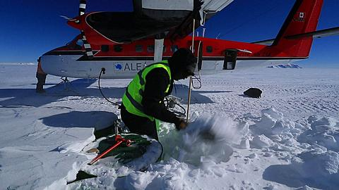 Twin otter aircraft being refueled in Antarctic wind, digging fuel drums out of snow