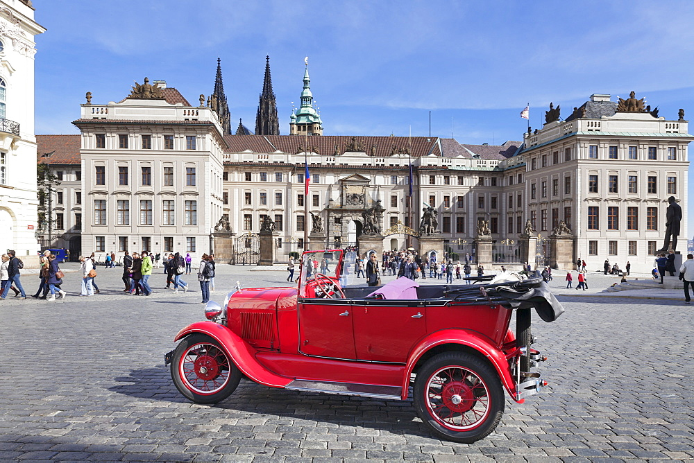 Red Oldtimer for tourist sightseeing tours in front of the First courtyard, Hradcany Square, Castle Hradcany and St Vitus cathedral, Castle District, UNESCO World Heritage Site, Prague, Bohemia, Czech Republic, europe