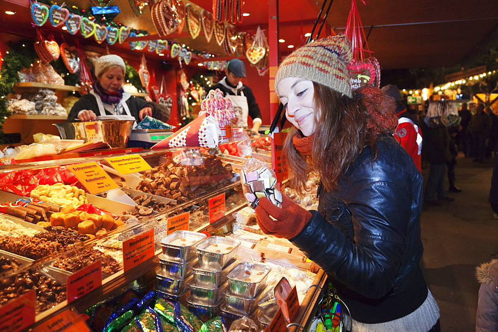 Young woman at the Christmas Fair looking at gingerbread, Esslingen am Neckar, Baden Wurttemberg, Germany, Europe