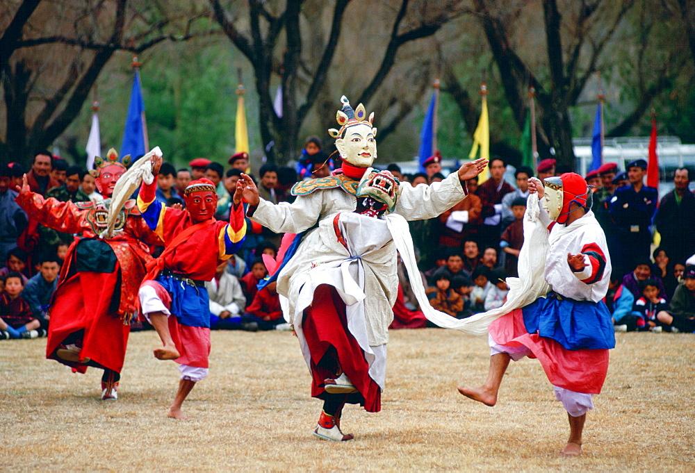 Dancers in masks enacting tales of Buddhist legend at festival, Paro, Bhutan