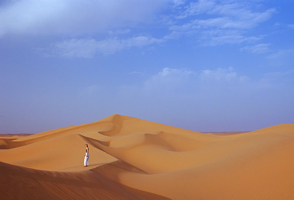 Tourists climbing up a sand dune in the Sahara Desert, Morocco
