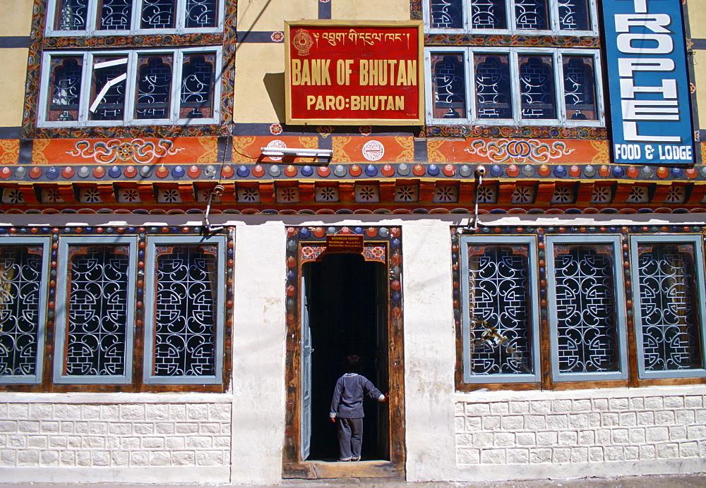 Small child standing in the doorway of the bank in Paro, Bhutan