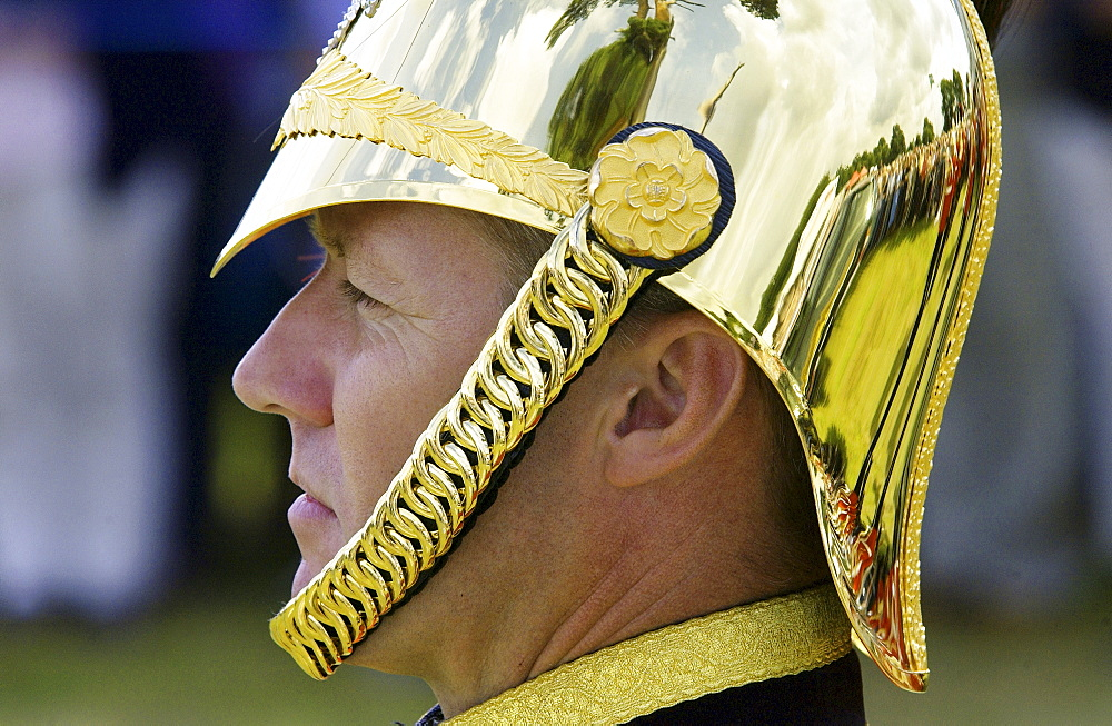 Man wears a brass helmet with chain chin strap,England