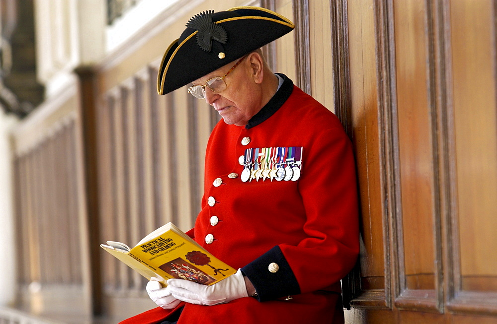 Chelsea Pensioner Alan Gale at the Royal Hospital Chelsea in uniform with his military medals reading a book on wood carving