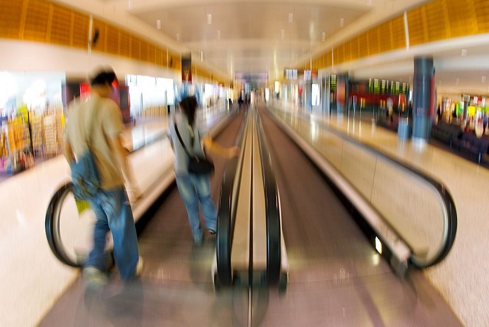 Commuters on an airport conveyor belt , Australia